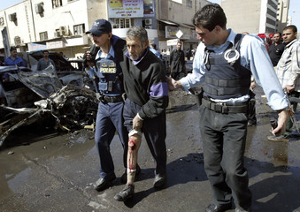 Iraqi police officers assist an injured man from the scene of car bombing in central Baghdad