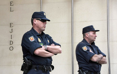 Spanish policemen stand at the entrance of the town hall of El Ejido