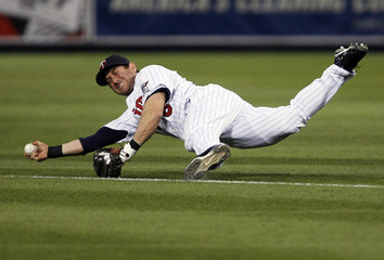 Minnesota Twins Nick Punto dives for a hard grounder off the bat of New York Yankees Melkey Cabrera but can't make the play in Minneapolis