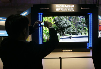 An attendee takes a photo of a Panasonic flat panel 150-inch High Definition plasma television during the Consumer Electronics Show in Las Vegas