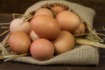 Chicken eggs with straw in bag on wooden background