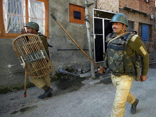 Indian policemen chase away Kashmiri protesters during anti-India protest in Srinagar