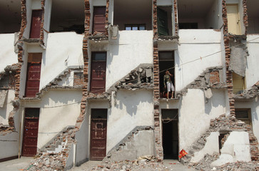 A resident stands inside a half-demolished residential building in Hefei