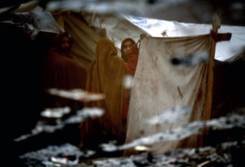Kashmiri earthquake survivors are reflected in mud pool in Alkhedmet refugee camp