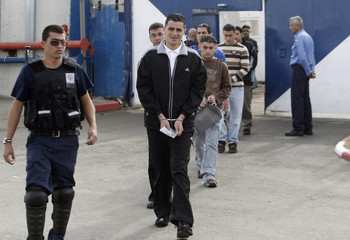 Palestinian prisoners walk with Israeli prison guard before their release from Ofer prison outside West Bank city of Ramallah