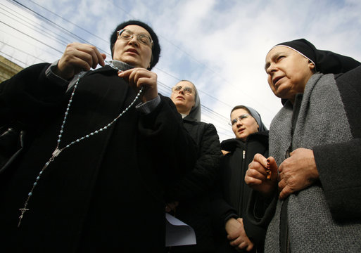 Romanian Catholic nuns pray during a protest against the construction of a modern office building to be built near the Saint Joseph cathedral in Bucharest