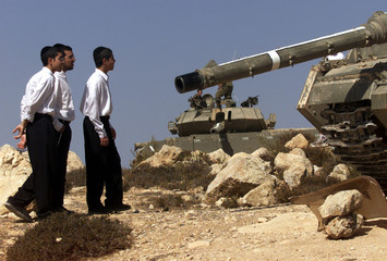 Young Jewish ultra-Orthodox men look over Israeli army Centurion tanks that are positioned October 8..