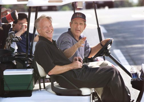 U.S. President George W. Bush rides from the 18th green with his old college friend and playing part..
