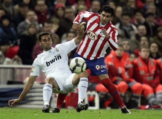 Atletico Madrid's Reyes battles for the ball with Real Madrid's Arbeloa during their Spanish First Division soccer match at Vicente Calderon stadium in Madrid