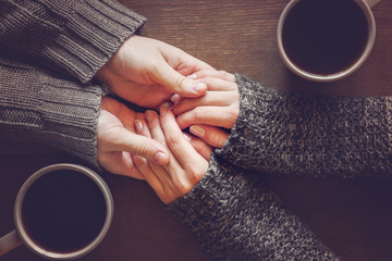 Man holding woman's hands. Young couple enjoying coffee and lovely conversations in the romantic evening atmosphere.