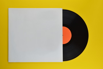 old black vinyl record with blank orange label halfway out of its white blank cover on yellow...