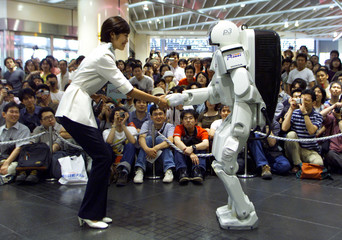 Honda's humanoid robot P3 shakes hands with Satomi Kojima, an employee of Honda, during a demonstrat..