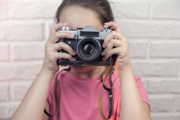 Young girl with an old photo camera