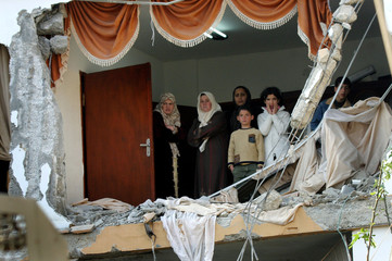 Palestinians stand inside building demolished by Israeli troops during Israeli operation in Yamun