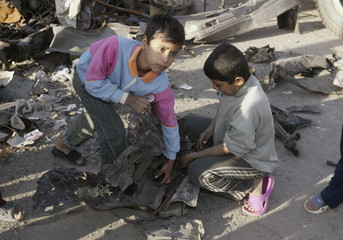 Children collect debris from a vehicle used during Tuesday night's car bomb attack in Baghdad's Sadr city