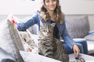 Young woman smiling and looking her Cat
