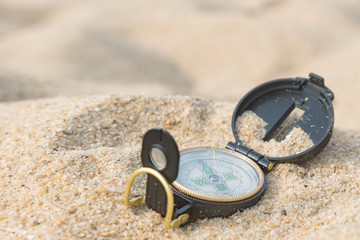 Compass in a beach sand. Compass lying on sea hot sand. Horizontal view