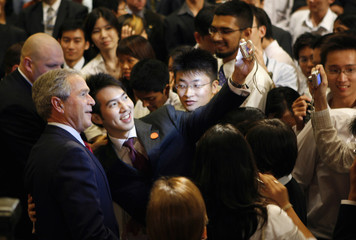 U.S. President George W. Bush poses for a photo with students after speaking at the National University of Singapore