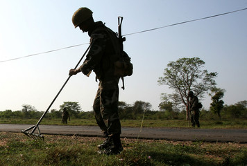 Sri Lankan army soldiers look for explosive devices along a road near Trincomalee in eastern Sri Lanka