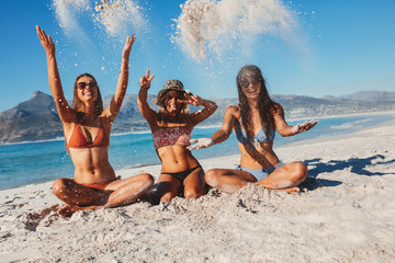 Female friends sitting on sandy beach and having fun