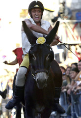 A rider of the San Antonio district whips his mount Pirandello during the annual donkey races in Umbria