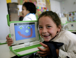 """First grade student of """"Treinta y Tres Orientales"""" elementary school in Villa Garcia, a poor neighborhood in the outskirts of Montevideo, shows a drawing she made using her XO laptop computer in her classroom"""