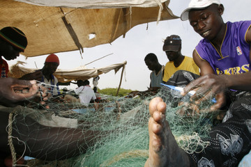 Fishermen repair their nets at a fishing port of Bissau