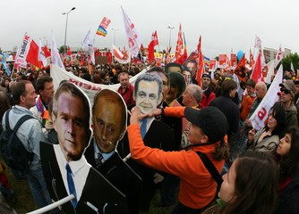 A protestor grabs a cardboard cut out of a G8 leader during an anti-G8 demonstration in Rostock