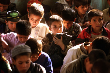 Afghan boys sit on the floor as they attend class in a home-based school in Kabul December 2, 2001. ..
