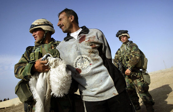A wounded Iraqi man begs to be released to see his injured family members in central Iraq March 29, ..