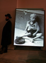 An ultra-Orthodox Jewish visitor stands alongside a photograph of a starving child during a visit to..