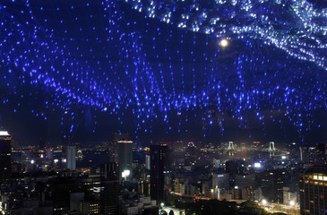A light display of the Milky Way is reflected on a window as skyscrapers and the Tokyo Bay area are seen in background from a viewing deck of Tokyo Tower