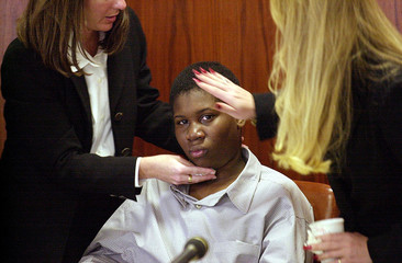 LIONEL TATE IS COMFORTED BY DEFENSE TEAM MEMBERS.