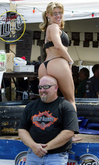 WOMAN SITS ON BALD MANS HEAD AT HARLEY-DAVIDSON PARTY IN WISCONSIN.