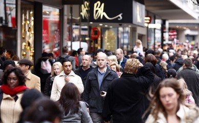 Shoppers walk along Oxford Street on Christmas Eve in central London