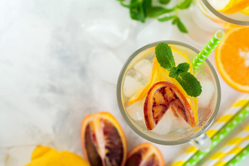 Cold and refreshing infused detox water with  orange, lemon and ice  in glass on a light background. Selective focuse.