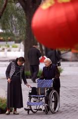 AN ELDERLY WOMAN PUSHES HER OWN WHEELCHAIR DURING A WALK THROUGH A PARKIN BEIJING.