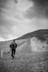 A backpack wearing runner heads up a hill towards stormy clouds