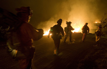 Firefighters hike towards flames during wildfire in Buckman Springs