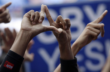 Supporter of Democratic Party makes sign of party's symbol during rally led by Indonesian President Yudhoyono in Jakarta