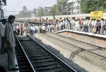 RAILWAY COMMUTERS STAND ON TRAIN TRACKS IN BOMBAY.