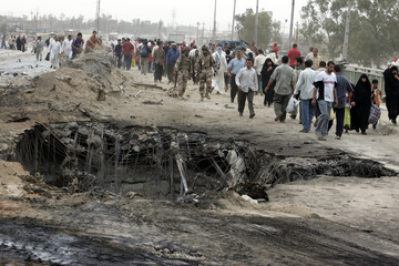 Residents walk on the destroyed Diyala bridge the morning after suicide bomb attacks in Baghdad