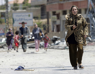 A Lebanese woman flees the viilage of Aitaron to Bent Jbail