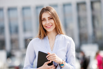 happy successful businesswoman in blue shirt holding touch pad and smiling