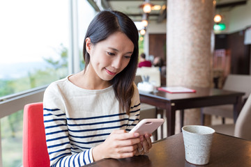 Woman sending sms on cellphone in cafe