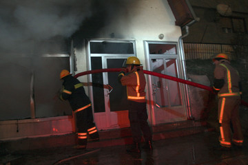 Firefighters try to extinguish fire in a shop in Kosovo's ethnically divided town of Mitrovica
