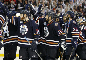 Edmonton Oilers players celebrate after defeating Caroline Hurricanes to win Game 6 in their NHL Stanley Cup ice hockey finals in Edmonton