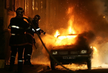 Firemen extinguish a burning car in Strasbourg's northern suburb of Cronenbourg November 7, 2005. He..