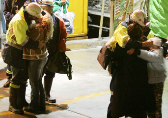 Tasmanian miners Russell and Webb hug family members after being rescued from the Beaconsfield gold mine