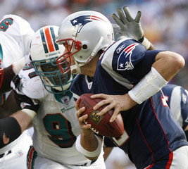 New England Patriots quarterback Tom Brady scrambles as Miami Dolphins Vonnie Holliday pressures him out of the pocket during second half NFL football action in Miami